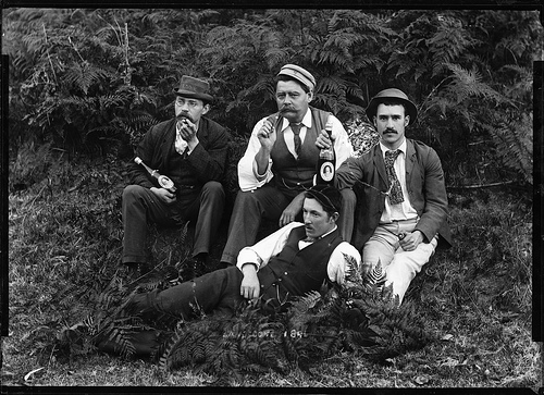 Four well-dressed men holding beer bottles. Australia. 1896.