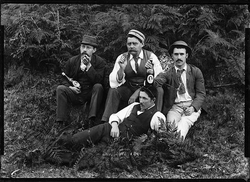 Four well-dressed men holding beer bottles. Australia. 1896.