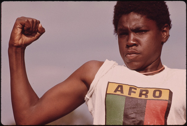 A Young Black Man Showing His Muscle during a Small Community Program in Chicago on the South Side, 08/1973